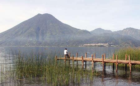 Een man wacht op de boot om hem in het meer