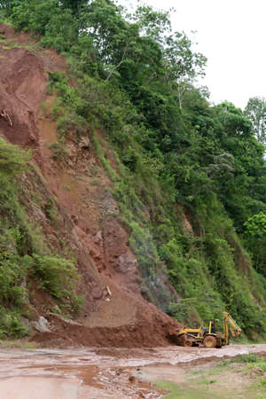 A backhoe moves dirt and mud from a mudslide along a highway Stock Photo