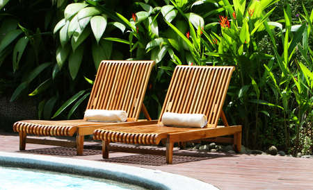 Resort lounge chairs surround an elegant pool Stock Photo - 2461582