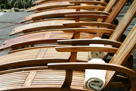 Wooden lounge chairs awaiting pool guests