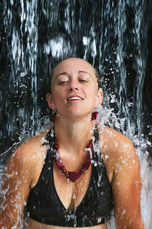 A young woman unwinding under a waterfall at a resort in central america Stock Photo - 2461568