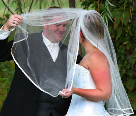 A happy wedding couple. The groom lifts the bridal veil Stock Photo - 2461553