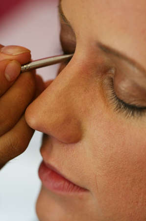 A young model has makeup applied before the big show