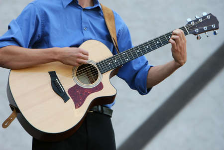 played: A classic six string guitar being played by a young man