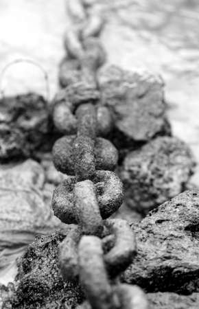 An old chain rests on volcanic rocks and leads into the ocean Stock Photo - 3396568