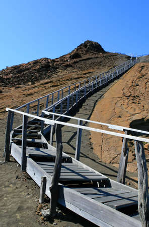 Wooden steps lead to the top of a barren rock in the Galapagos islands photo