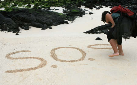 castaway: A castaway write a SOS message in the sands in hope of rescue
