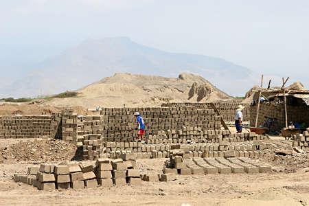 Werknemers bereiden modder bakstenen in de woestijn