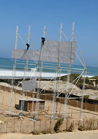Workers construct a new billboard sign on the coast of Peru photo