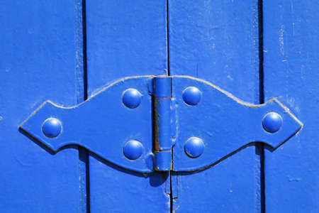 hinge: A brightly painted blue hinge on a wooden gate