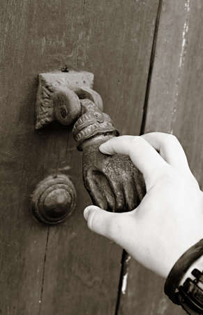 A female hand knocks an old-fashioned hand door knocker Stok Fotoğraf