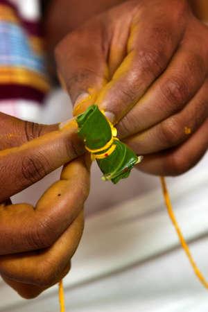 Un pr?tre hindou pr?pare une noix d'arec envelopp?e dans une feuille de b?tel dans le cadre d'un Bengali pr?-c?r?monie de mariage Banque d'images - 5534231