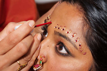 A Red Bindi is applied to a Hindu brides forehead photo