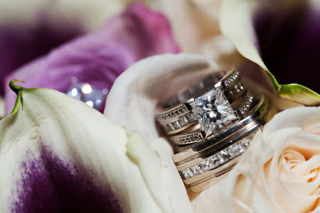 Diamond wedding rings on a flower background Stock Photo