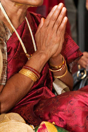 A woman prays during a Hindu ceremony photo