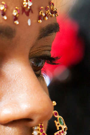 A closeup of the face and nose ring of a young Indian brde