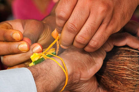 A nut and leaf are tied to the wrist in a Hindu pre-wedding ceremony photo