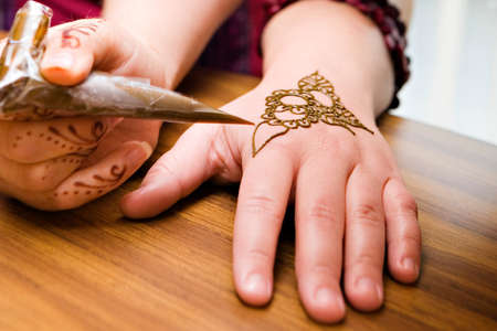 A young american woman gets henna applied to her hands