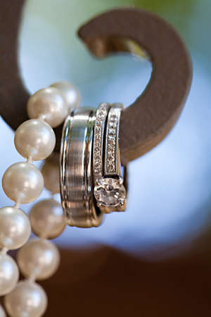 A close-up shot of beautiful wedding rings hanging with pearls
