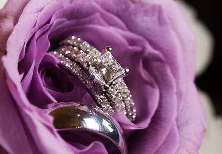 A close-up shot of a beautiful wedding ring inside a purple rose