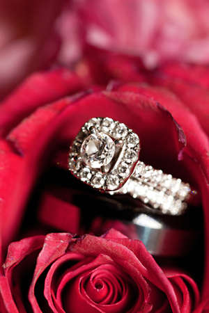A close-up shot of a beautiful wedding ring inside a red rose photo