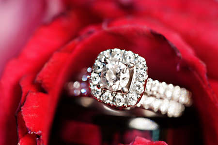 A close-up shot of a beautiful wedding rings inside a red rose