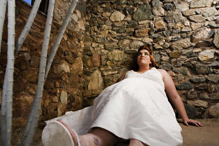 A beautiful plus size bride with green eye make-up posing in her wedding dress photo