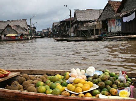 rise above: Fruit for sale on a boat. Houses on stilts rise above the polluted water in Belen, Iquitos, Peru. Thousands of people live here in extreme poverty without clean water or sanitation. Stock Photo
