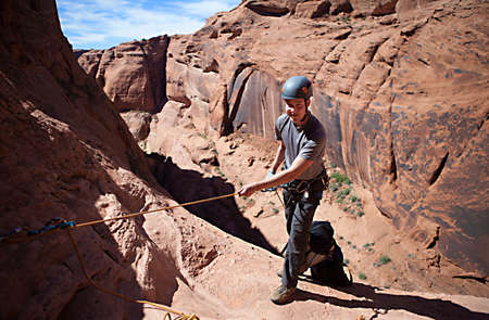 rappel: A young man prepares to rappel into a technical canyon in northern Arizona, USA Stock Photo