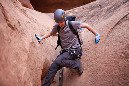 stemming: A young man down-climbs in a sandstone slot canyon Stock Photo