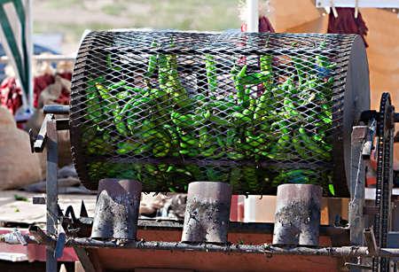 Groene chilis zijn vuur geroosterd in een grote metalen trommel