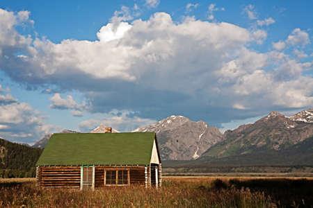 Log Cabin below Grand Teton mountain range in Wyoming, USA Editorial