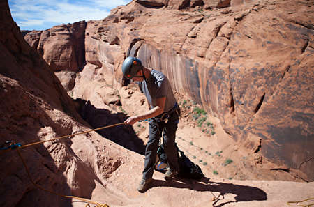 abseil: A young man prepares to rappel into a technical canyon in northern Arizona, USA