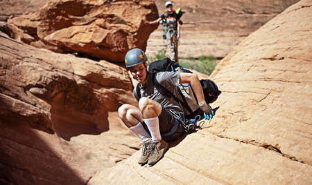 abseil: A young man slides down a steep sandstone face in an Arizona slot canyon