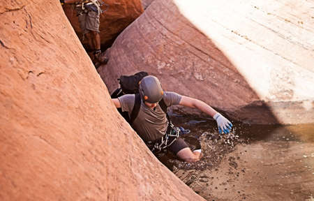 abseil: A young man explores a wet technical slot canyon in northern Arizona, USA