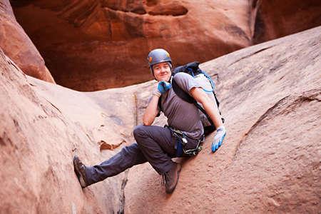 A young man explores a technical slot canyon in northern Arizona, USA photo