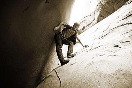 Performing a tricky down-climb in a narrow slot canyon in Arizona, USA photo