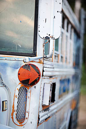 junked: An orange arrow turn-signal on an old school bus Stock Photo