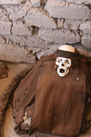 tiedup: This pre-incan mummy is preserved by the dry desert air with hair intact. Skulls and bones in Chauchilla, an ancient cemetery in the desert of Nazca, Peru. On the left is hair wrapped all the way around the body.