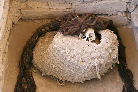 mummification: This pre-incan mummy is preserved by the dry desert air with hair intact. Skulls and bones in Chauchilla, an ancient cemetery in the desert of Nazca, Peru. The remains of many people, some still with long hair, can be seen.