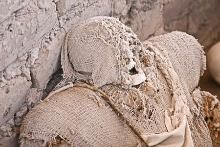This pre-incan mummy is preserved by the dry desert air with hair intact. Skulls and bones in Chauchilla, an ancient cemetery in the desert of Nazca, Peru. The remains of many people, some still with long hair, can be seen.