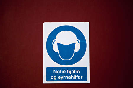 A sign in icelandic that hard hats and ear protection are required