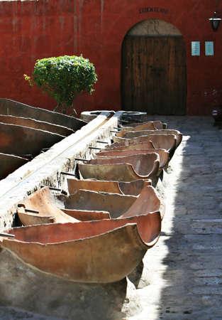 anforas: Lavandería al aire libre en el Monasterio de Santa Catalina, Arequipa, Perú. Un canal de piedra envía el agua para lavar bañeras hechas de ánforas de división