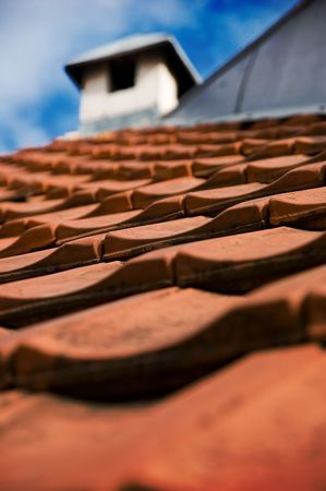 Roof with red tiles and chimney Stock Photo