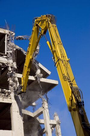 buildingsite: Destruction of concrete wall of old building with excavators