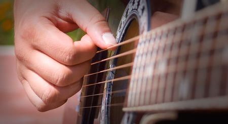 ballad: Playing acoustic guitar - great shot detail of a guitarist hands