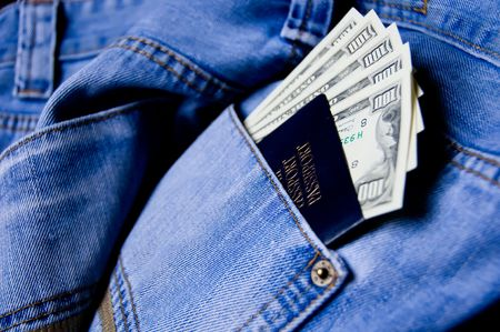 Passport with American dollars in the pocket of jeans