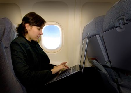 Business woman using laptop during the flight Banque d'images