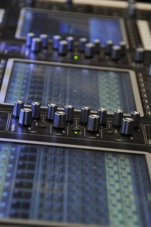 Audio mixing board with several channels and push sliding buttons photo