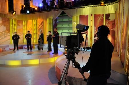 news reporter: Cameraman works in the studio - recording show in TV studio Editorial